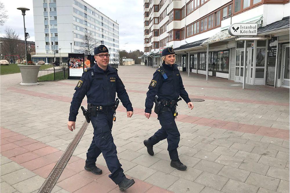 Två patrullerande poliser på ett torg.